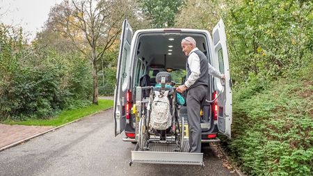 A senior retired man helping to transport disabled people Banco de Imagens