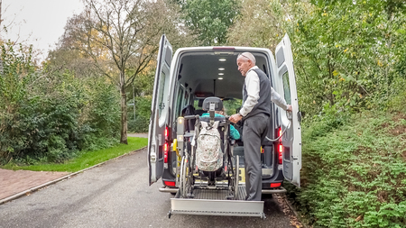 A senior retired man helping to transport disabled people Imagens