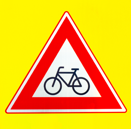 A red triangle beware of cyclists warning sign on a yellow background Imagens