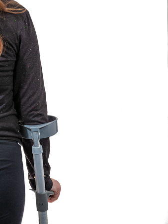 A young handicapped girl walking with crutches.