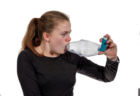 A young girl using an inhaler for asthma