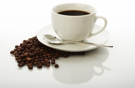 grano de cafe: Taza del café con leche con los granos de café Foto de archivo