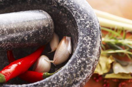 Mortar with thai spices (garlic, chili, pepper, lemon grass) Stock Photo