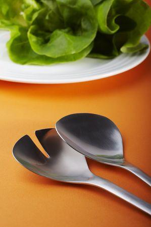 Salad spoon and fork on orange background