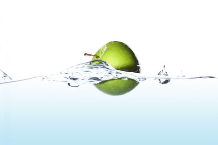 Isolated green apple surfing on the wave Stock Photo