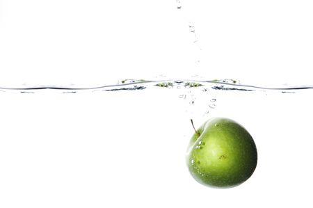 dropped: Apple cay� al agua en el fondo blanco Foto de archivo