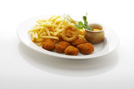 papas fritas: Nuggets, franc�s fritas y aros de cebolla fritos en el plato Foto de archivo