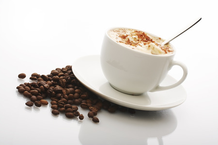 coffee cup with cream top on the plate with coffee beans