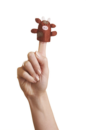 Isolated girls hand with finger puppet (farm animal: cow) photo