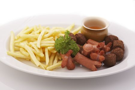French fries, meatballs and sausages on the plate over a white background photo