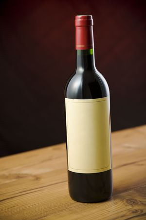 Red wine bottle on wooden table over dark red background Stock Photo - 2379816
