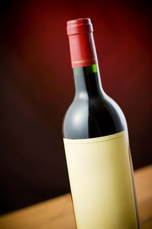 cabarnet: Red wine bottle on wooden table over dark red background
