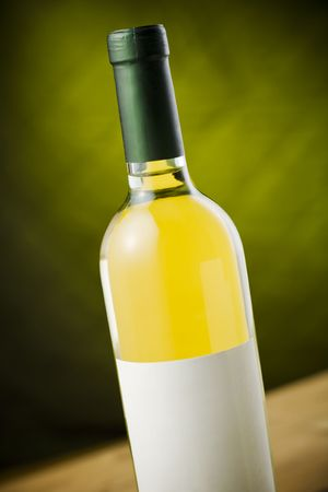 White wine bottle on wooden table over dark green / yellow background Stock Photo - 2379809