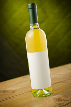 White wine bottle on wooden table over dark green / yellow background Stock Photo - 2379815