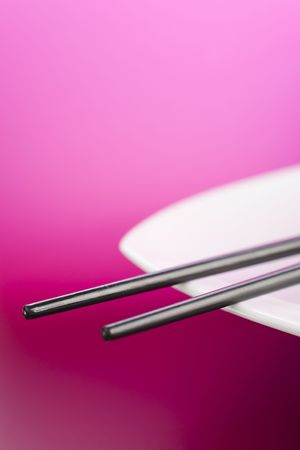 Chopsticks on the white plate over pink background Stock Photo