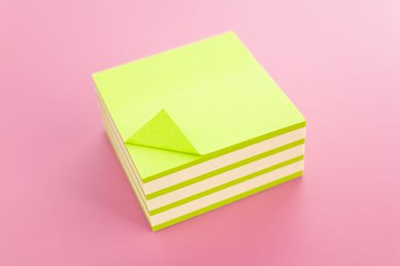 writing utensil: Pile of sticky notes over a pink table Stock Photo