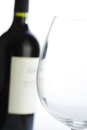cabarnet: Close up of glass with red wine bottle on background