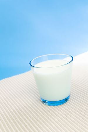 Glass filled with milk over a blue background Stock Photo - 2630693