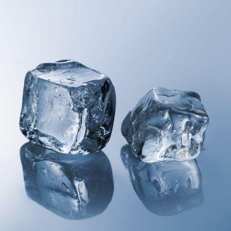 cubos de hielo: Cubitos de hielo en la reflectantes de color azul claro de mesa  Foto de archivo