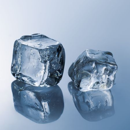 Ice cubes on the reflective light blue table