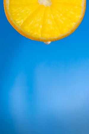 backlit orange slice over the blue background