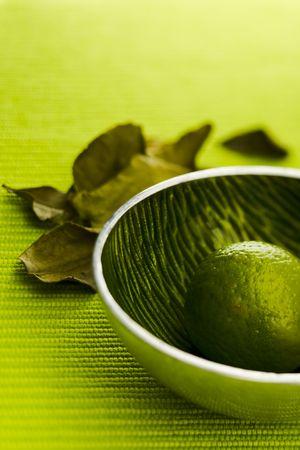 kafir lime: Lime with kafir leaves on the green table Stock Photo