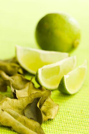 kafir lime: Lime with kafir leaves on the green table (shallow dof) Stock Photo