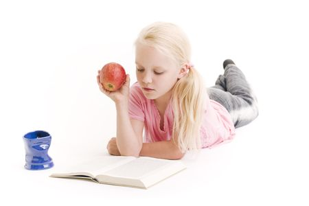Young girl reading a book and eating an apple photo