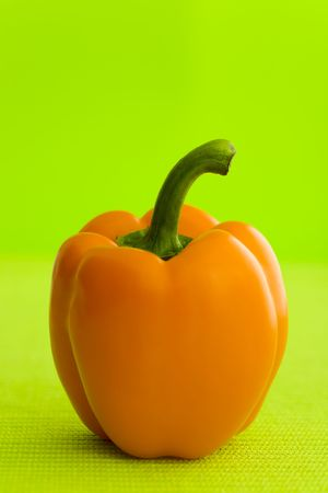 belly pepper: Single orange pepper over the green background