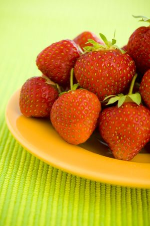 Strawberries piled on the yellow plate over lime background photo