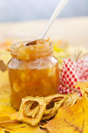 Full jar of apple jam on the leaves