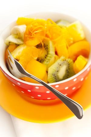 Fruit salad on the white dotted bowl (kiwi, orange, pinapple, banana etc). photo