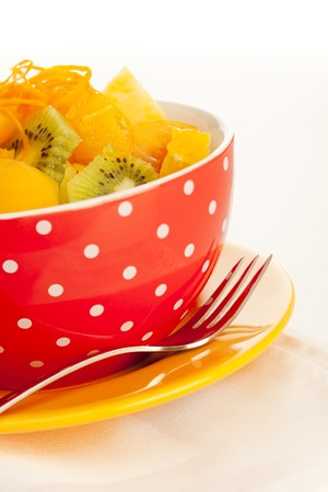 Fruit salad on the white dotted bowl (kiwi, orange, pinapple, banana etc). photo