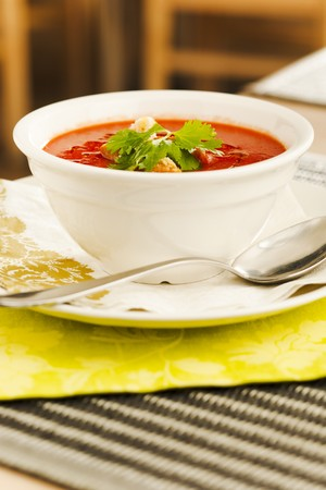 Tomato soup with bread crumps and leaves photo