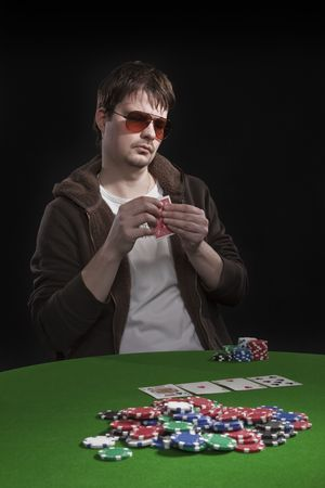 Man with sun glasses playing poker on green table. Chips and cards on the table. photo