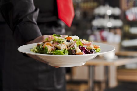 Waiter handing a green salad to customer Stock Photo