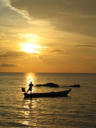 Fisherman casting his nets at sunset, Ko Lanta, Thailand