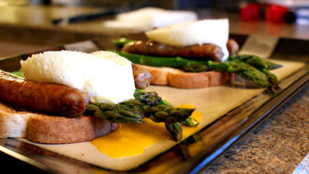 Breakfast Sandwich - Asparagus, poached egg and breakfast sausage on toast  Imagens