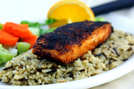 Blackened salmon served on wild rice with vegetables  Imagens