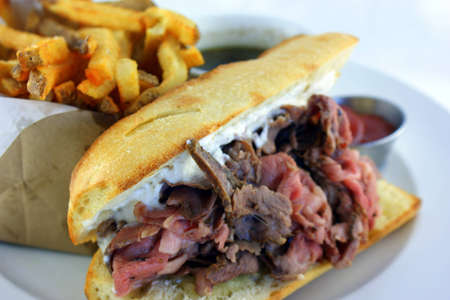 French Dip Sandwich - Juicy smoked prime rib sandwich on a crunchy French baguette smeared with horseradish sauce, and thinly sliced medium rare prime rib and Swiss cheese Stock Photo - 15323114