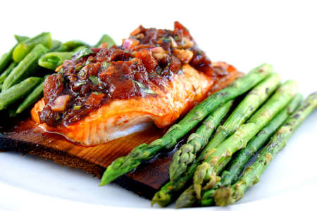 food and drink: Cedar planked salmon served under roasted tomato vinaigrette and accompanied by sugar snap peas and blistered asparagus  Stock Photo