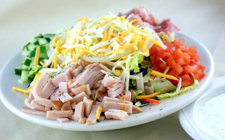 Chopped salad with turkey, ham, cucumber, tomato, iceberg lettuce, onion and cheese