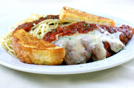 Fresh breaded veal topped with marinara sauce with spaghetti and garlic toast  Imagens