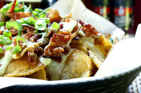 Homemade potato chips with cooked smoked bacon, creamy blue cheese and scallions