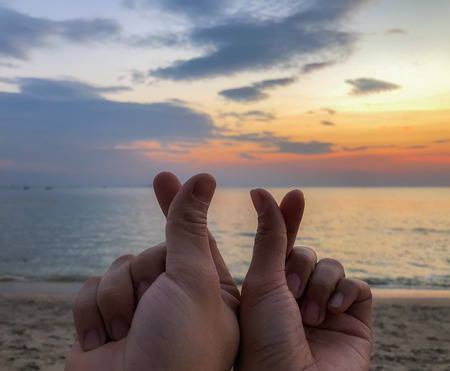 The couple's hands show Korean mini heart sign hand in front of sunset background on the beach.