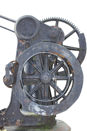 flywheel: Cast-iron handwhell with a gearwheel, part of a historic english hand crane  Objects separated from background on white  Stock Photo