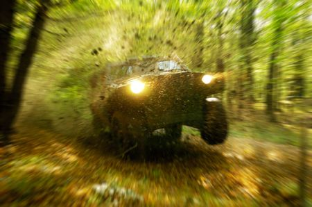 Military off-road vehicle storming through forest photo