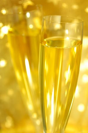 fresh graduate: Close-up view of flute Champagne glasses on golden starry background, selective focus on the glass, shallow DOF