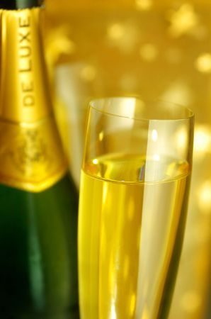Close-up view of a flute glass and a bottle of Champagne on golden starry background, selective focus on the glass, shallow DOF photo
