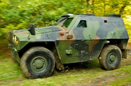fourwheeldrive: Military off-road vehicle driving on a forest dirt road, ripping leaves and small branches hanging over the road. Blurred wheels and vegetation in the background.